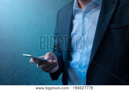 Handsome businessman in modern business suit using mobile phone for everyday job tasks communication e-mail correspondence and newsletter reading