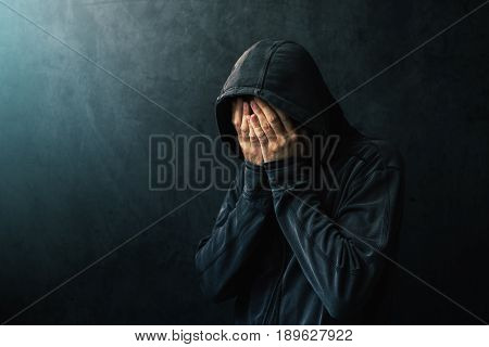 Desperate man in hooded jacket is crying hands are covering face and tears in the eyes light of hope shining from his right side