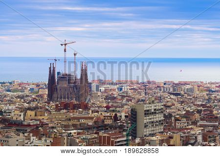 Barcelona Spain - 1 April 2017: Beautiful view on Sargada Familia being constructed and a cityscape of Barcelona in cloudy weather view from the Park Guell.