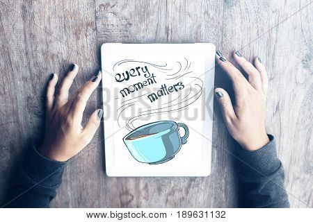 Top view of female hands holding white tablet with text and coffee cup on screen. Wooden background. Every moment matters