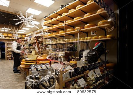 GRONINGEN, NETHERLANDS - DECEMBER 31, 2016: Employee in the cheese store on Ubbo Emmiusstraat. The cheese shops offer a wide variety of Dutch cheese and is very popular among culinary tourists