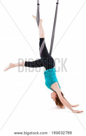 Young woman practices aerial anti-gravity yoga with a hammock in a white studio