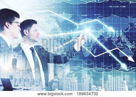 Two attractive businessmen drawing downward forex chart arrows on city background. Sales concept. Double exposure