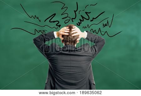 Back view of stressed young businessman on chalkboard background with scribble. Worried concept