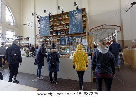 HELSINKI, FINLAND - APRIL 8, 2017: People buying food in the Old Market Hall. The building was opened for customers in 1889