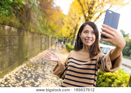 Woman taking selife with cellphone at street