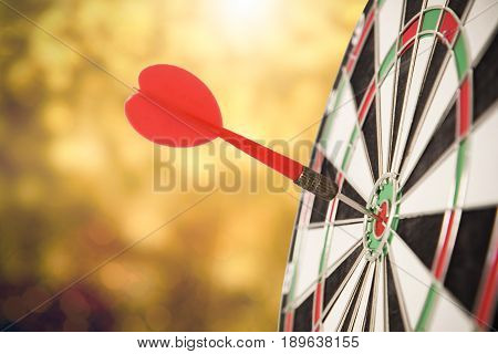 target red arrow center of dartboard blurred bokeh background. concept business goal to marketing success.