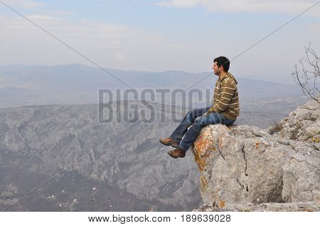 Young man sits on a cliff edge on the top of mountain with gorgeous view. Enjoying the view on the edge of the cliff