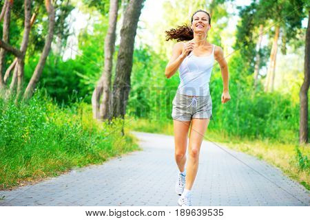 Beauty young Woman running in the park. Young sporty girl jogging with earphones outdoors. Workout. Healthy lifestyle. Full length portrait