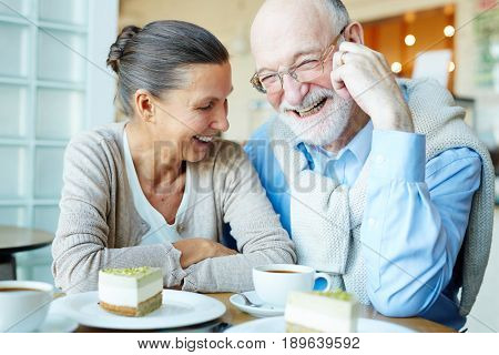 Joyful spouses having fun in cafe at leisure
