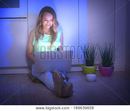 Beauty student girl sitting on a floor at night and using laptop computer at night. Online shopping, e-shopping. Woman at home buying online in internet, studying or chatting with friends in dark room