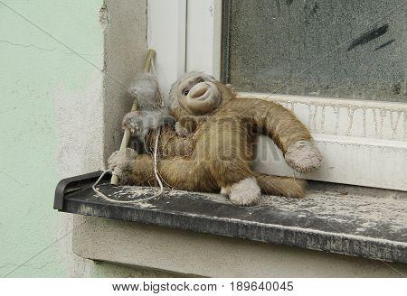 dirty damaged toy monkey left on the window of abandoned house
