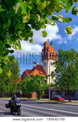 Firehouse building in Riga on a background of green trees and passing by on the street biker