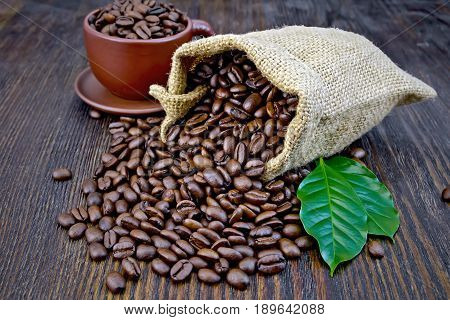 Coffee Black Grains In Bag With Cup And Leaf On Board