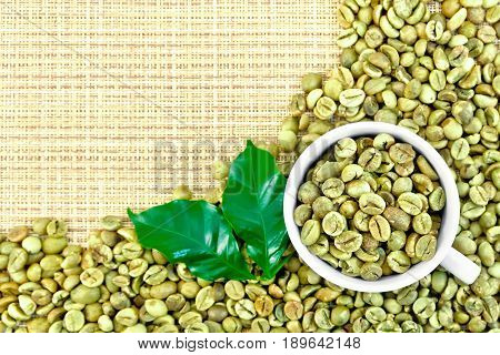 A frame of green coffee beans with leaves and a cup on a yellow coarse woven fabric