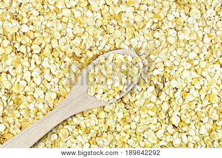 Texture of yellow pea flakes with a wooden spoon