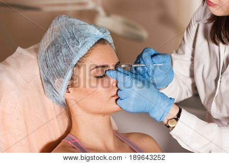 Woman gets injection in her face. Beauty woman giving injections. Young woman gets beauty facial injections in the cosmetology salon. Face aging injection. Aesthetic Medicine, Cosmetology.