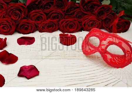 Red carnival mask lies on a white wooden table in the background of a bouquet of roses