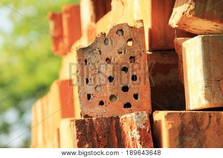 orange brick with holes closed by solitary bees used as insect hotel