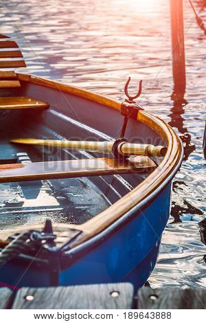 Wooden pleasure rowboat at the pier of a lake at evening sunset light. Alster. Hamburg. Germany