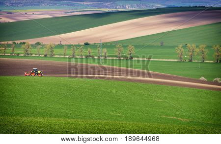 Agricultural landscape with tractor plowing a striped brown field in South Moravia at sunset beautiful view on rolling hills Czech Republic. It is a magical place nicknamed the Czech Tuscany.