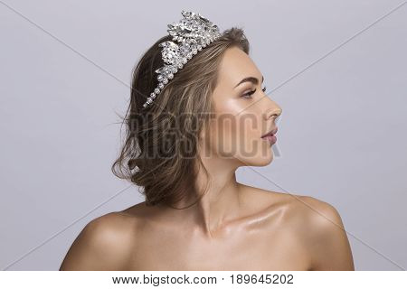 Portrait of beautiful young blonde woman with a diadem on a head