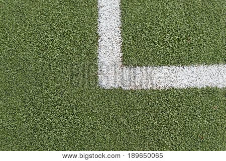 Green synthetic grass sports field with white line