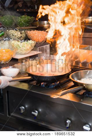 Chef in restaurant kitchen at stove with pan doing flambe on food