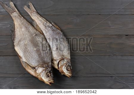 Dried fish on the table. Salty dry river fish on a dark wooden background.top view
