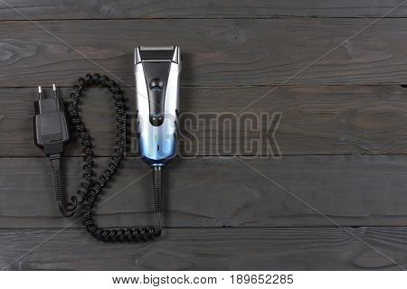 Electric shaver on wooden table top view with copy space