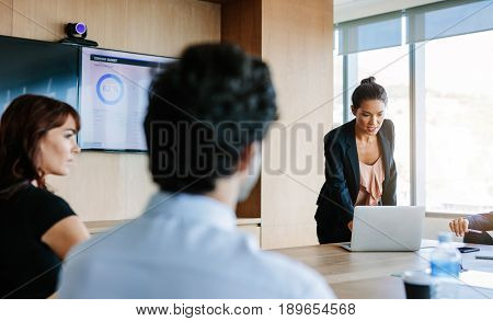 Group of business people have meeting at conference room and having discussion about new ideas. Asian businesswoman explaining plans to colleagues using laptop.