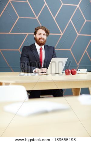 Happy newsreader with laptop sitting by workplace in tv studio