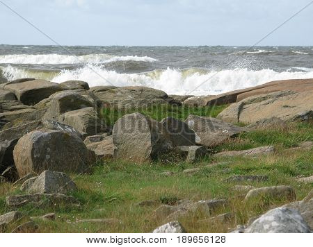 Rocky coastal landscape with seaspray at Skrea Strand on a sunny and windy day with dark clouds in Falkenberg Sweden.