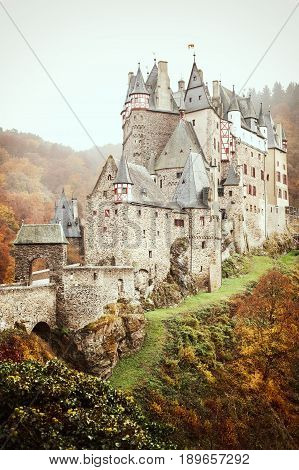 Burg Eltz picturesque medieval castle at the rhine valley Germany. Fall season in hills above the Moselle River between Koblenz and Trier Germany.Colored outdoors vertical image.