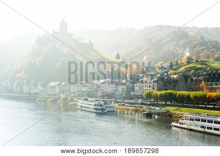 Early morning foggy landscape with town Cochem along the river moselle with reichsburg castle and vineyard valley in rays of sunlight. Panoramic view. Multi-colored horizontal outdoors autumn image.