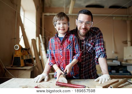 Man and boy in protective eyewear carving wooden planks in workshop
