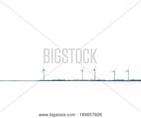 Wind power turbines coastal placement with white sky and ocean abstract image.