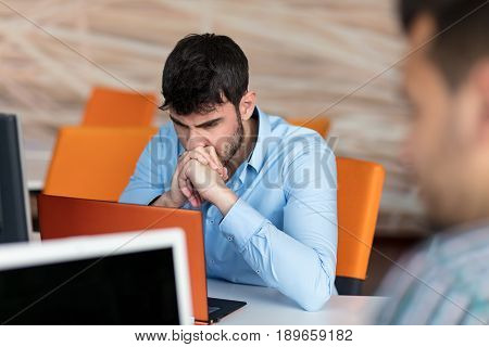 Worried businessman working at his desk in his office.