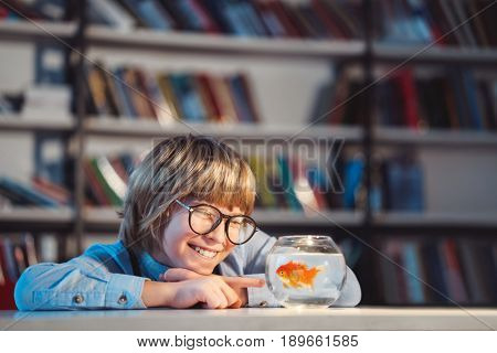 Smiling boy with a goldfish in library
