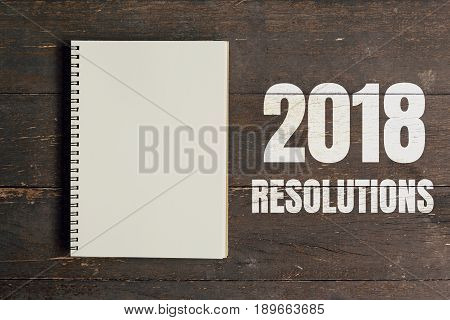 2018 Resolutions And Brown Note Book Open On Wood Table Background With Space.