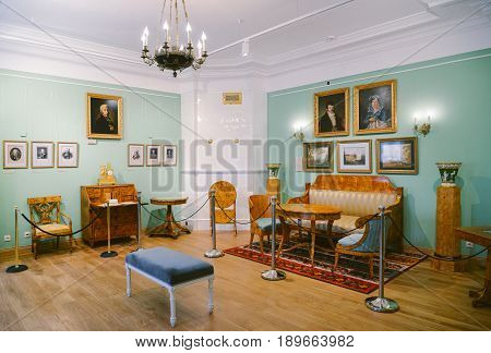 Ostafyevo, Moscow region - May 13, 2017 - Antique living room in the estate Ostafyevo. Old furniture from Karelian birch and stripes silk. Sofa, armchairs, table, bureau, portraits, watch, vases.