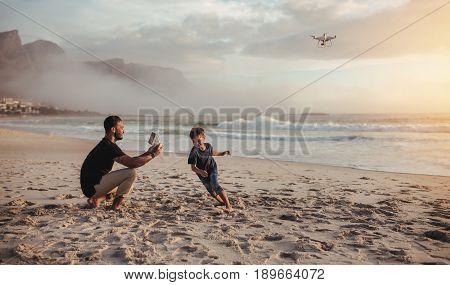 Father Flying Drone And Son Running On Beach