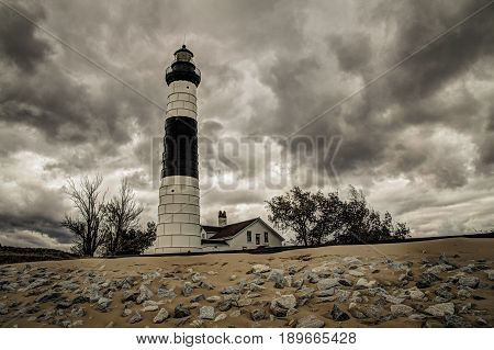 Storm On The Horizon. Dark storm clouds surround the Big Sable Point Lighthouse on the remote shores of Lake Michigan in Ludington State Park in Michigan's Lower Peninsula.