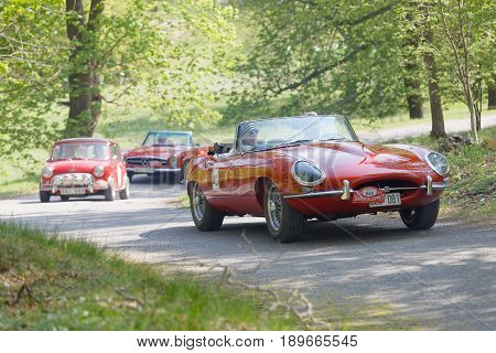 STOCKHOLM SWEDEN - MAY 22 2017: Red Jaguar E-Type classic car from 1965 driving on a country road in the public race Gardesloppet in the forests at Djurgarden Stockholm Sweden. May 22 2017