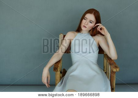 Portrait of a confident redhead girl having appraising glance at copy space wall sitting in a chair on a dark blue background. Gorgeous female model wearing blue dress resting and posing in studio