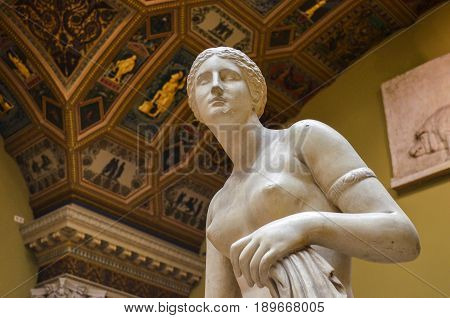 Moscow, Russia - October 04, 2016 - Pushkin state museum of fine art. Statue of greek goddess of love Aphrodite on the blurred background of the painted ceiling with column.