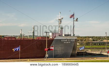 Sault Ste Marie, Michigan, USA - May 31, 2014: A massive Great Lakes freighter at Soo Locks. The Locks are the busiest in the world with over 500 billion dollars of iron ore transported through them.