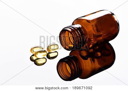 Bottle Of Glass With Cod Liver Capsules On Grey Surface