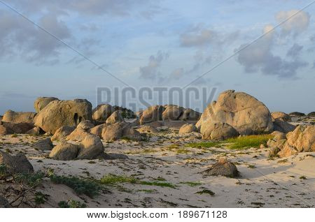 Large limestone rock formations on the white sand beach on Aruba's north shore.