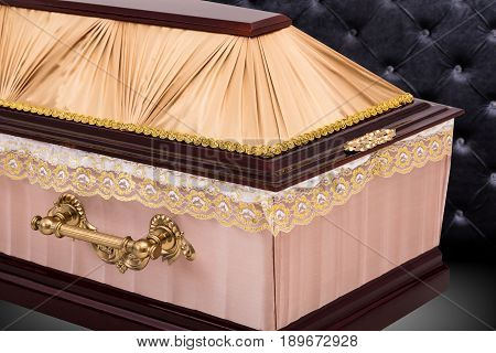 closed wooden beige coffin covered with cloth isolated on gray luxury background. coffin close-up with shadow on royal background. Ritual objects for burial. Surrender body dust of the earth. Christian funeral ritual